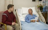 image of hospital patient  - Son visiting his Dad in the hospital - JPG