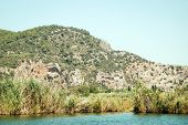 pic of dalyan  - Distance view on ruins of Lycian rock tombs seen from Dalyan River near ancient city Kaunos in Turkey - JPG