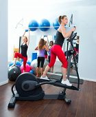 Aerobics cardio training woman on elliptic crosstrainer bicycle at gym