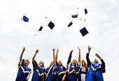 image of toga  - Image of happy young graduates throwing hats in the air - JPG