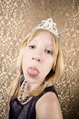image of spoiled brat  - Portrait of pretty pouting young girl wearing a tiara with her tongue out - JPG