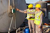two industrial engineers inspection fuel tank in chemical plant