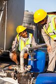 foto of pressure point  - two petrochemical workers inspecting pressure valves on a fuel tank - JPG