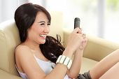 stock photo of handphone  - young beauty girl sitting on sofa and hold the handphone - JPG