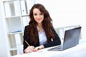 stock photo of thoughtfulness  - Young pretty business woman with notebook in the office - JPG