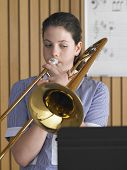 High school girl playing trombone in music class