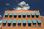 stock photo of ybor city  - A red brick building with two rows of teal window shades against a blue sky with white fluffy clouds - JPG