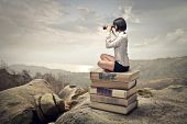 picture of binoculars  - beautiful woman sitting on a pile of old books watching with binoculars - JPG