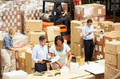 stock photo of lift truck  - Workers In Warehouse Preparing Goods For Dispatch - JPG