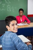 Portrait of happy teenage schoolboy sitting at desk with teacher in background