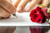 foto of sweethearts  - Man writing a letter to his sweetheart or lover for Valentines or an anniversary with a red rose lying alongside the notepaper view of his hands - JPG