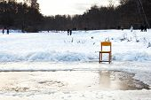 pic of epiphany  - icebound chair near opening water in frozen lake after orthodox epiphany holiday in cold winter evening