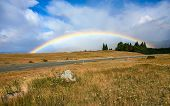 Beautiful full rainbow over road and mountain New Zealand