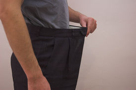 picture of bulging belly  - Close up on slimmed down male waistline wearing old trousers to demonstrate weight loss - JPG
