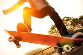 foto of skateboarding  - young skateboarding woman jumping on sunrise skatepark - JPG