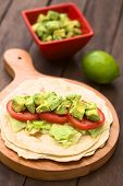 image of avocado  - Fresh homemade tortilla with lettuce tomato and avocado on wooden board with avocado salad and lime in the back  - JPG