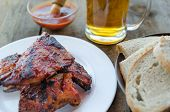 foto of marinade  - Spareribs on grill with hot marinade czech beer and bread - JPG