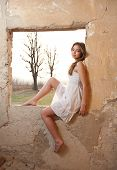 picture of short legs  - Sensual lady in white dress looking to the window and red sun behind her - JPG