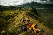 image of cross hill  - Group of hikers crossing rocky obstacle in the mountains - JPG