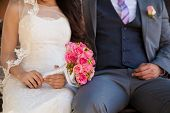 stock photo of boutonniere  - Closeup of a bride and groom sitting on a bench together on their wedding day - JPG