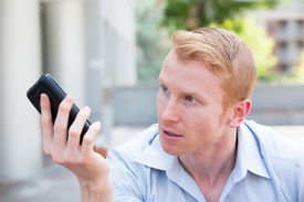 stock photo of pissed off  - Closeup portrait annoyed young man pissed off by what he heard or saw on his cell phone isolated outdoors background - JPG