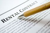 stock photo of rental agreement  - Filling a rental contract  with wooden pen - JPG