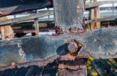 foto of neglect  - Part of a neglected wooden jetty with rusted iron beams and bolts from close - JPG