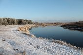 stock photo of paysage  - winter paysage river bank covering under snow and deep blue flow of  the river - JPG