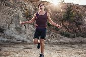stock photo of jump rope  - sporty man jumping rope outdoors in the morning - JPG