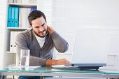 picture of frown  - Frowning handsome businessman having neck pain in the office - JPG