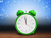 pic of count down  - Alarm clock counting down to twelve against shimmering light design over boards - JPG