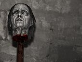 stock photo of beheaded  - Decapitated head lying on wooden stake after medieval Inquisition execution - JPG