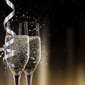 stock photo of flute  - Champagne flutes on black background - JPG