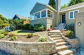 stock photo of stone house  - House exterior in clapboard siding and front yard landscape Stairs with stone trim - JPG