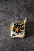picture of muse  - A jar of healthy swiss museli yogurg blackberries and honey on a black slate background - JPG