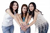 stock photo of gathering  - Portrait of three modern teen girls standing in the studio while gathering their hands - JPG