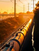 stock photo of railroad car  - Tank cars of a long freight train glow orange in the light of the rising sun - JPG