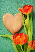 stock photo of orange blossom  - wooden heart and beautiful orange tulips over green textured paper background - JPG