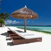 stock photo of boracay  - Sun umbrella and beach beds on tropical coastline Philippines Boracay - JPG