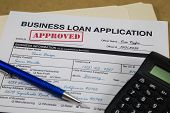 pic of borrower  - Approved Business Loan Application form with blue pen and a calculator - JPG
