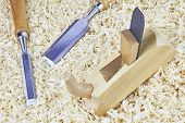 image of chisel  - Two chisels and one spokeshave lying in wooden shavings - JPG