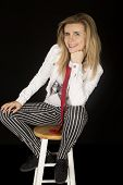 picture of stool  - Female model sitting on stool striped pants - JPG