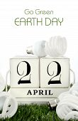 stock photo of save earth  - Earth Day April 22 concept with energy saving light bulbs surrounding white wood block calendar - JPG