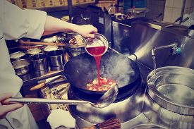 stock photo of chinese wok  - Chef is pouring sour sauce in wok at commercial kitchen - JPG