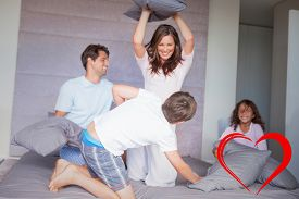 picture of pillow-fight  - Family having a pillow fight on the bed against heart - JPG