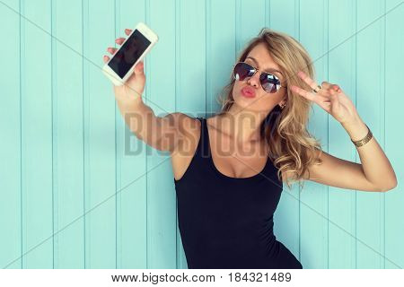 poster of blonde woman in bodysuit with perfect body taking selfie with smartphone  toned instagram filter