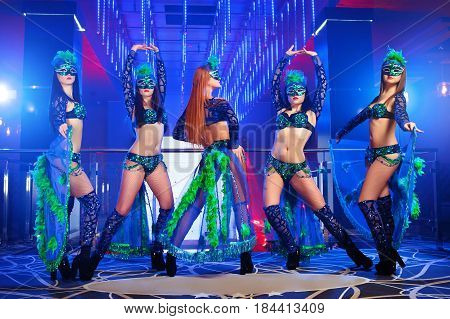 poster of Shot of five sexy professional dancers wearing matching carnival outfits and masks performing at the nightclub disco dancing performance entertainment costume erotic exotic showgirls concept.