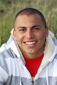 picture of crew cut  - Attractive young hispanic man smiles in outdoor portrait - JPG