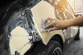 Repairing Car Body By Puttying Close Up Work After The Accident By Working Sanding Primer Before Pai poster