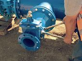 Worker Hands Screwing Gate Valve With Nuts On Piping. poster